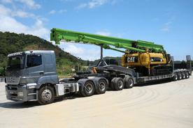 carreta prancha transportando máquina pesada para obra