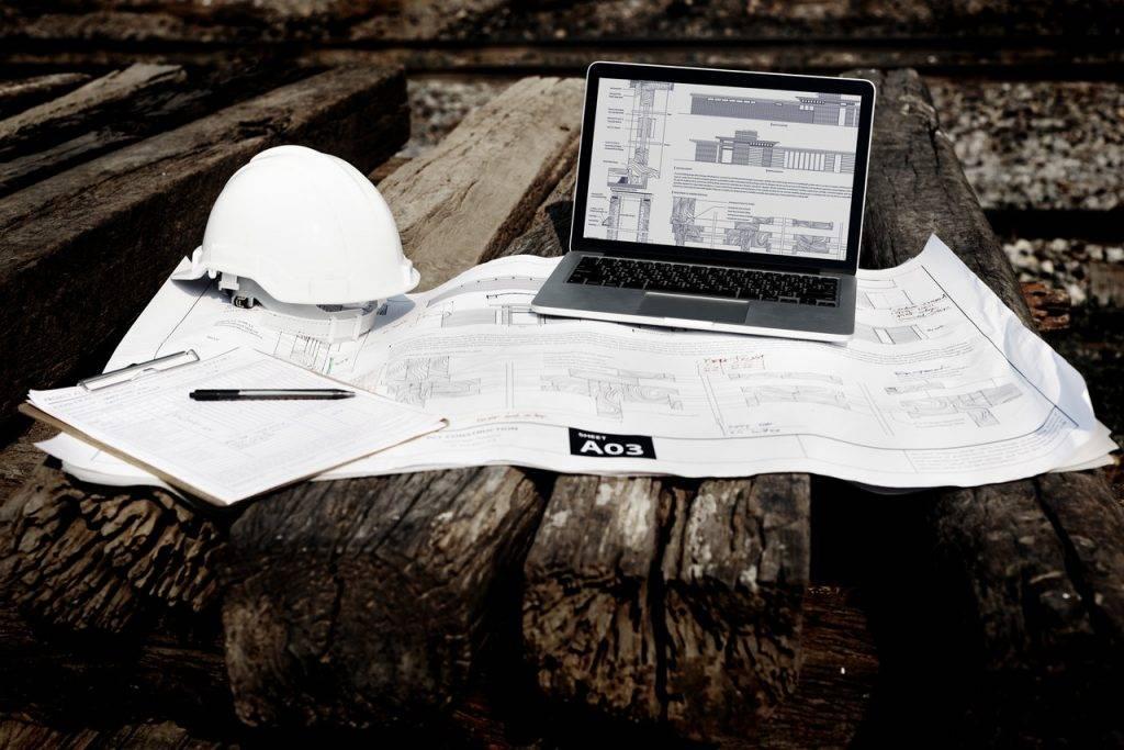 Imagem ilustrando o gerenciamento de obras, com um notebook, um capacete, um projeto e uma prancheta.